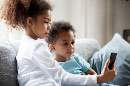 Pretty African American children using smartphone at home, little preschooler girl sitting together on couch with toddler boy holding phone in hands, taking photo, making selfie, watching video Stock Photo