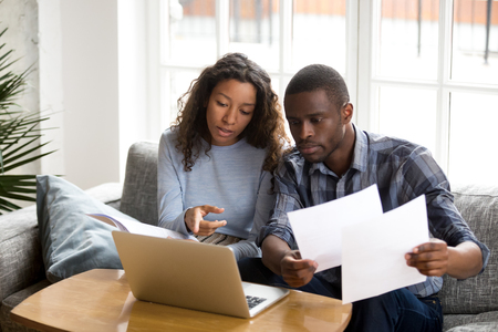 Serious African American couple discussing paper documents, sitting together on couch at home, man and woman checking bills, bank account balance, terms of contract, mortgage, loan agreement Stock Photo