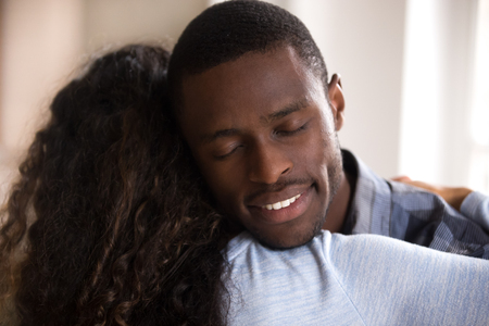 Calm loving African American husband embracing wife with closed eyes, affectionate couple in love, romantic relationship, loving man supporting woman rear view, gratefulness, close up 写真素材