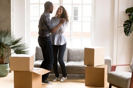 Gelukkige Afro-Amerikaanse verliefde paar dansen na verhuizing in nieuw huis, aantrekkelijke lachende vrouw en man vieren verhuizing, kartonnen dozen met bezittingen, huiseigenaren in nieuw appartement Stockfoto