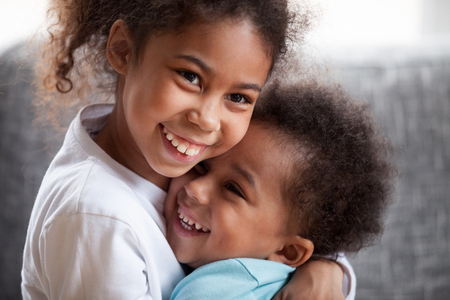 Happy African American siblings embracing, sitting together on couch at home in living room, little preschooler girl hug toddler adorable boy, good relations between sister and brother, close up 스톡 콘텐츠