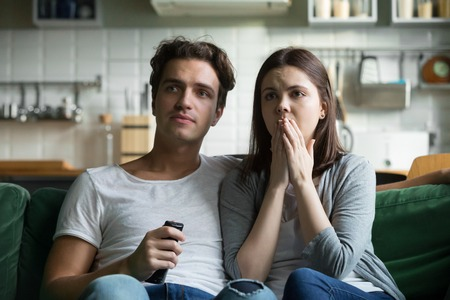 Young millennial sorrowful couple spend free time together sitting on couch at home. Girlfriend and boyfriend watch tv online tearful melodrama, sympathizes with the protagonist and unexpected ending Stock Photo