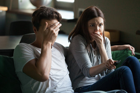 Young emotional frightened millennial married couple in love, boyfriend and girlfriend spending free time together sitting on couch at home. People watching online internet tv thriller scary movie. Stock Photo