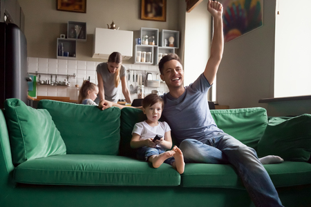 Toddler son with father watching football, baseball, basketball on TV together, excited, celebrating, rejoice at goal, victory of favorite team, mom and sister cooking, family spending time together