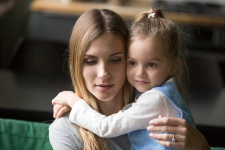 Little cute preschool girl embracing tired, upset mother, single mum with daughter, support, compassion, care, help, say sorry, good relationships of mum and child, motherhood