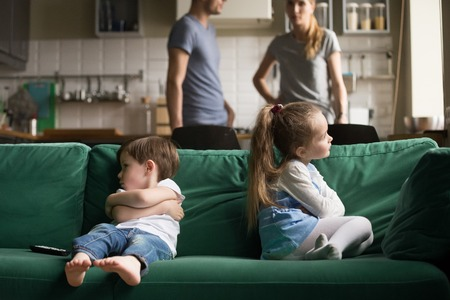 Upset offended toddler brother and sister sitting separately on couch, sofa with arms crossed, little girl and boy ignoring each other, not talking, puzzled parents discuss situation Stockfoto