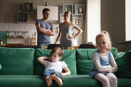 Upset offended sister, daughter sitting separately on couch with arms crossed with toddler brother on couch, sofa after fight about tv channel, cartoon choice, little girl and boy ignoring each other Stockfoto