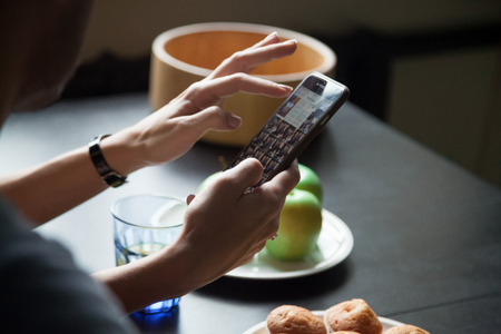 Female hands holding smartphone and showing photos to man, young woman demonstrating gallery on phone during breakfast, looking for photo, hand view close up