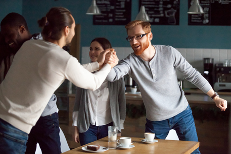 Excited millennial friends greeting, hanging together in cafe, smiling guy get acquainted with colleague at friendly meeting in coffeeshop, diverse students reunited in cafeteria embracing say hello
