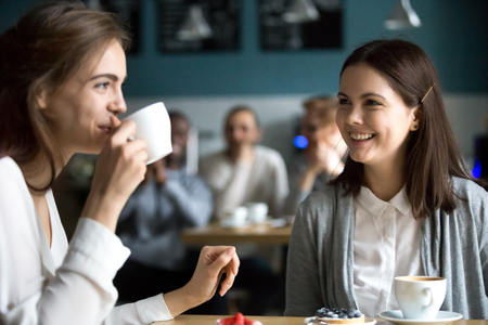 Beautiful young girls sitting in cafe enjoying coffee having fun together, pretty millennial females spend time in coffeeshop meeting for drink, smiling students hang out in cafeteria laughing