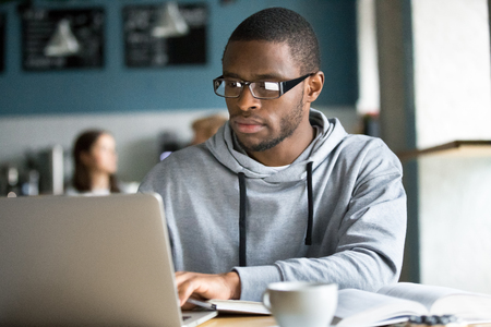 Serious black guy in glasses work at laptop sitting in coffeeshop, concentrated African American student study online at computer having coffee in near cafe, focused afro use gadget browsing internet Stock Photo