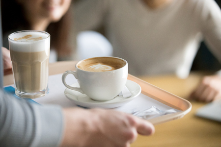 Close up of waiter holding aromatic cappuccino and latte on tray bringing order to cafe guests, coffeeshop worker give hot drinks to visitors, cups with delicious fresh brewed coffee on platter Banque d'images - 114277352
