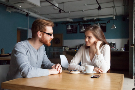Millennial red-haired man approaching beautiful young girl enjoying coffee and dessert in cafe, interested young guy get acquainted with pretty female, young people flirt sitting in coffeeshop