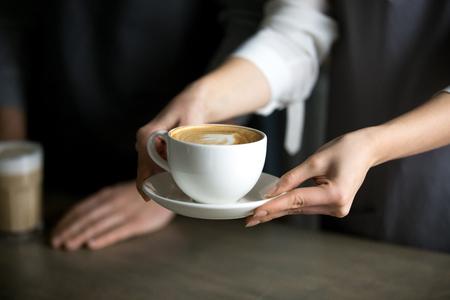 Cerca de barista sosteniendo capuchino aromático, sirviéndolo al visitante de la cafetería, camarera dando una taza de café recién hecho con espuma de leche al invitado de la cafetería, llevando bebida con leche a la mesa de la cafetería Foto de archivo