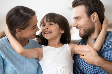 Portrait of multi-ethnic attractive mother father adorable little preschool daughter sitting together looking at each other embracing. New parents for adopted child or happy wellbeing family concept