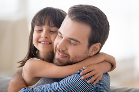 Portrait smiling loving handsome Caucasian father and adorable preschool mulatto daughter indoors. Daddy and child closed eyes embracing sitting on couch at home. Friendly multi-ethnic family concept Stock Photo