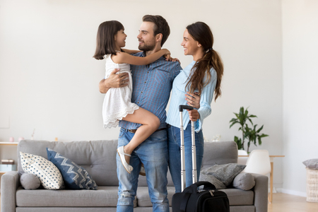 Happy wife husband married couple and daughter standing in living room at home. Father hold kid on hands. Family feels happy going on vacation together suitcase luggage is ready for journey adventure