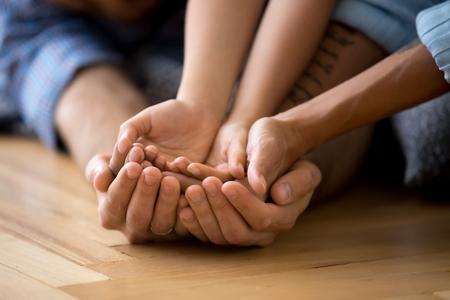 Paumes de mains familiales empilées sur un plancher en bois chaud. Mère fille et père bras se bouchent. Concept de soutien et d'amour, de compréhension et de dévotion, de liens et de relations chaleureuses entre les gens