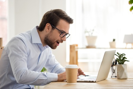 Excited male worker look at laptop screen reading breaking news, surprised man using computer get unexpected email offer or promotion letter, lucky employee feel euphoric win lottery online Stock Photo