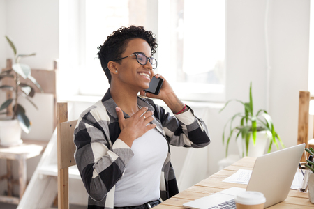 Happy black woman sit at wooden office desk work at laptop having pleasant call or cell conversation, African American girl in glasses smile talking on smartphone at workplace, female speak on phone
