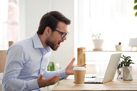 El trabajador de sexo masculino enojado pierde los estribos grita en voz alta teniendo problemas con la computadora o ataque de virus, el hombre furioso grita la experiencia de avería de la computadora portátil o la pérdida de datos mientras trabaja, el empleado enojado recibe un mensaje de error en la PC