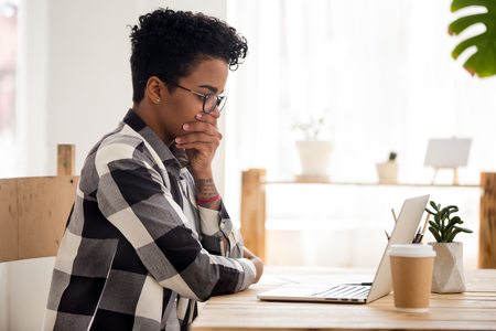 Stressed African American female in glasses look at laptop read bad online news, depressed black girl feel down receive negative response or dismissal email, afro woman upset with message on computer