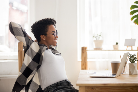 Happy African American girl in glasses stretch in chair satisfied with finished laptop work, smiling black female relax leaning back looking at computer screen achieve good result. Reward concept