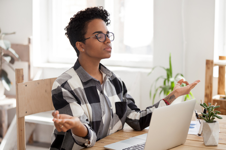 Calm African American female in glasses meditate at workplace control emotions, peaceful black woman take break distracted from computer work practice yoga with mudra hands. Stress free life concept