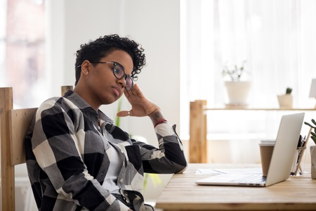 Exhausted African American girl bored at workplace look at laptop screen wait for inspiration, relaxed black female think about problem solution, pondering over decision. Dull monotonous work concept Imagens
