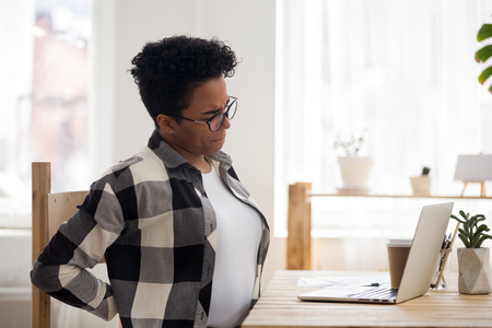 Exhausted black girl stretching in chair working at laptop long in uncomfortable position, stressed African American woman massage back having spinal spasm or strain. Sedentary lifestyle concept 스톡 콘텐츠
