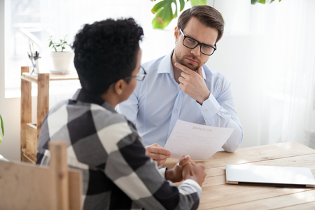 Suspicious male employer look at African American millennial applicant, doubt in candidature, thoughtful HR manager consider resume hesitating about black candidate experience at office interview Фото со стока - 114277604