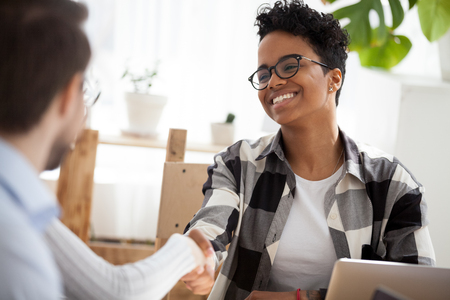 Smiling African American woman handshake colleague at office meeting introducing, happy black female employee in glasses shake hand of coworker getting acquainted at casual business briefing