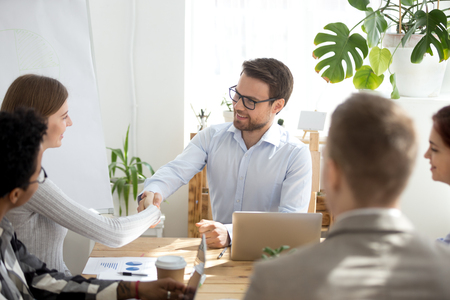 Smiling millennial male ceo or boss shake hand of female employee get acquainted during office meeting, businessman handshake woman worker happy introducing or greeting during briefing Stockfoto