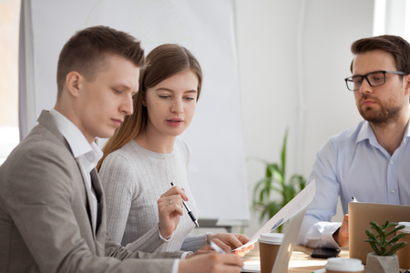 Serious millennial colleagues talk analyzing company document or financial statistics, focused employees speak collaborating or brainstorming at meeting, woman explain paperwork to male worker