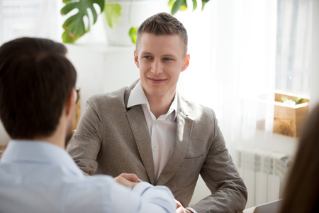 Back view of male employee shake hand of colleague during office business meeting, businessmen handshake at negotiations getting acquainted, partners greeting or introducing at briefing Stockfoto