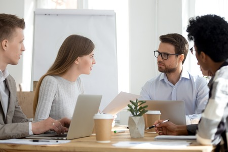 Millennial diverse employees talk brainstorming or collaborating at office meeting, workers sit at shared table with laptops cooperating at casual briefing, colleagues analyze statistics or paperwork
