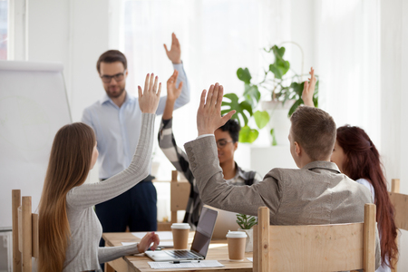 Diverse employees raise hands engaged in teambuilding activity during business mentor or coach flipchart presentation, multiethnic colleagues participate in education training during meeting Stockfoto
