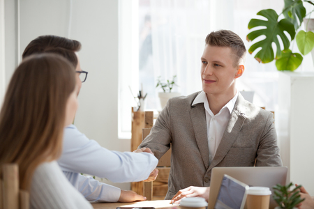 Smiling millennial businessman sit at table heading meeting shaking hand of male colleague, employees handshake at briefing getting acquainted or introducing, man greeting worker at workplace Foto de archivo