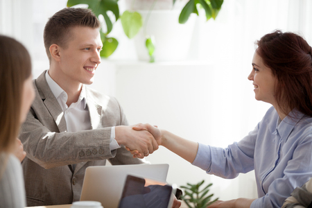 Smiling businessman shake hand of young female colleague getting acquainted at workplace, diverse employees handshake introducing at meeting, smiling man greeting coworker woman at briefing Stockfoto
