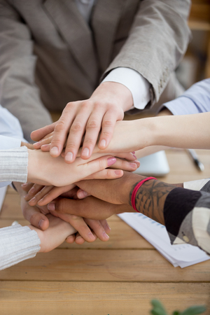 Close up of multiracial workers join hands together in stack show support, reach shared goal, diverse people engaged in teambuilding activity or training at meeting, promise help. Cooperation concept