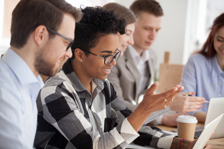 Smiling millennial multiethnic workers use laptops discussing projects at meeting together, diverse employees or students work at office meeting with computers, brainstorming or cooperating Stock Photo