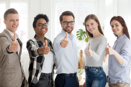Happy millennial multiracial people standing together showing thumbs up sign, smiling young employees or workers make gesture recommending good service, diverse colleagues give recommendation 版權商用圖片