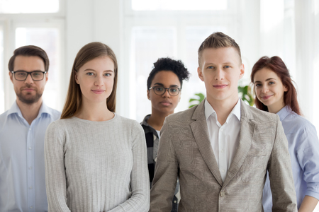 Portrait of successful millennial multiracial people stand looking at camera, team of young employees or workers smiling posing for picture together, diverse company professionals or staff in office Stock Photo