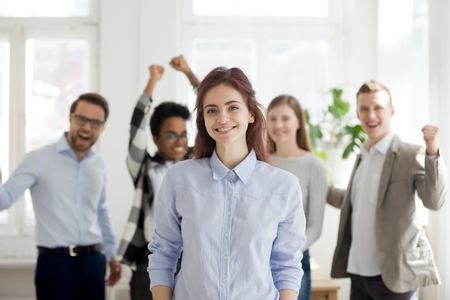 Portrait of smiling female employee standing foreground, excited team or colleagues cheering at background, successful woman professional look at camera posing in office. Leadership concept Stock Photo