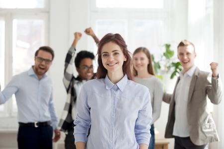 Portret van glimlachende vrouwelijke werknemer die op de voorgrond staat, opgewonden team of collega's die juichen op de achtergrond, succesvolle vrouw professionele kijken naar camera poseren in kantoor. Leiderschapsconcept