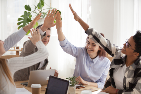 Happy millennial workers raise hands giving high five at teambuilding activity at meeting, smiling diverse colleagues sit at table having fun at briefing participating in training. Cooperation concept Foto de archivo