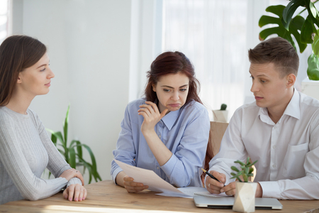Suspicious HR managers read candidate resume, doubting about experience and candidature, dissatisfied recruiters feel doubtful considering self-confident applicant CV at hiring. Bad interview concept Stock Photo