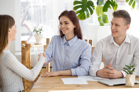 Smiling recruiter shake hand of female job candidate getting acquainted at interview in office, HR manager handshake work applicant greeting her or thanking for business talk. Employment concept