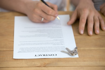 Close up of husband sign contract buying house from  broker, man put signature on document, keys on table, taking mortgage or loan, renter finalize formal procedure closing deal with agent