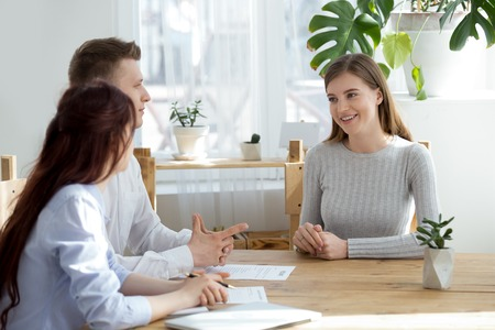 Happy millennial girl talk at work interview with HR managers, recruiters listen to female job applicant speak at hiring or recruitment process, confident candidate make good first impression